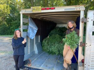 two women with trailer of harvested hemp